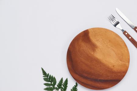 Leere Holzschale mit Messer und Gabel auf weißem Hintergrund, Draufsicht Standard-Bild