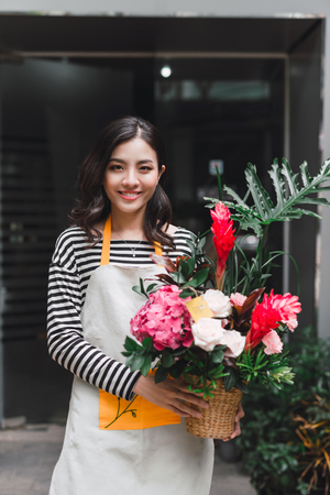 Beautiful asian female florist is standing in flower shop and holding bouquet of flowers