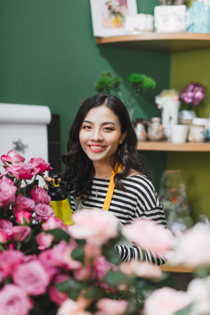 Pretty young florist with bouquet in flower shop Stock Photo