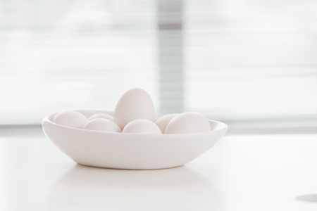 Eggs on white plate on wooden table Stock Photo