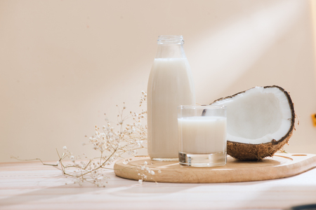Coconut milk in bottle and glass on table with copy space Stok Fotoğraf