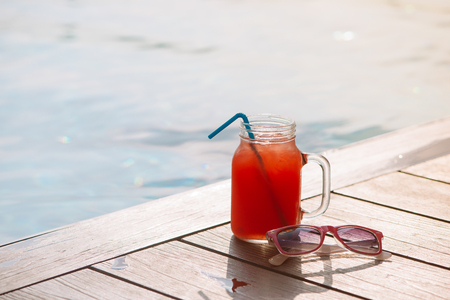 Glass of fresh watermelon smoothie juice drink on border of a swimming pool - holiday tropical concept
