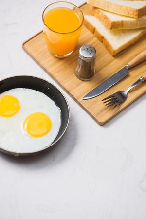 fried eggs in a frying pan, toast and orange juice for breakfast on a white background.