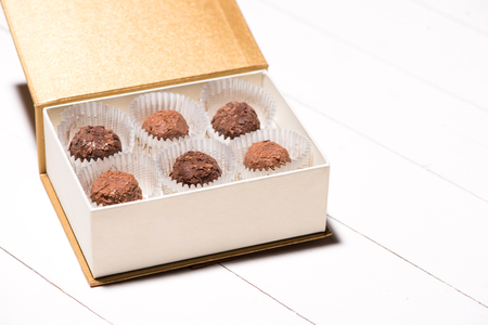 A lot of variety chocolates in box on white wooden background
