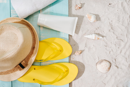 Beach accessories flip flops, sunglasses, hat and orange juice on wooden deck