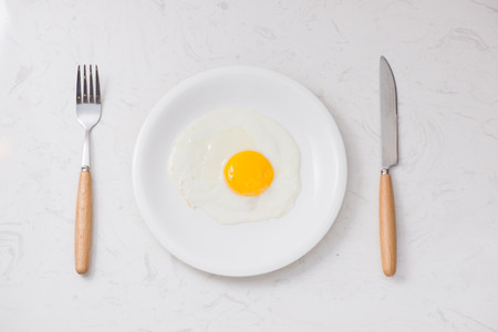 Top view of white dish with fried egg on white background.
