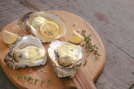 Tasty fresh oysters with sliced lemon on cutting board. Aphrodisiac food for increasing sexual desire