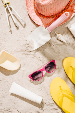 Top view of sandy beach with glasses and summer accessories. Background with copy space and visible sand texture. Border composition made of towel