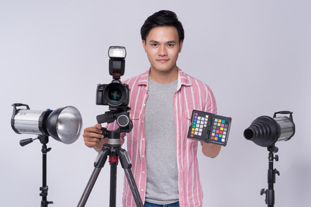 Young asian photographer holding digital camera, while working in studio Stock Photo