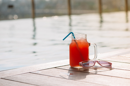 Glass of fresh watermelon smoothie juice drink on border of a swimming pool Banco de Imagens