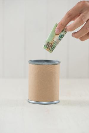 Putting money into donation box.