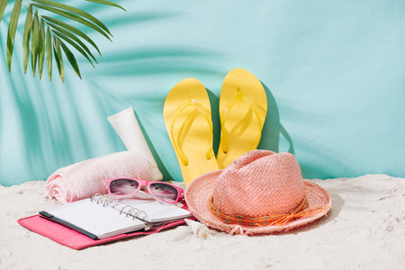 Summer accessories on sandy beach. Summer exotic relaxation concept. Copyspace for text