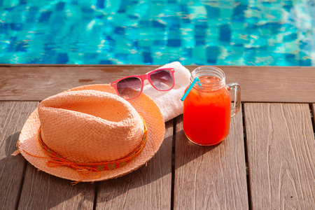 Fresh glass of water-melon smoothie drink with sunglasses, straw hat and slippers on border of a swimming pool Banco de Imagens
