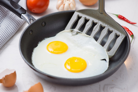 fried eggs in a frying pan for breakfast on a white background. Daylight.