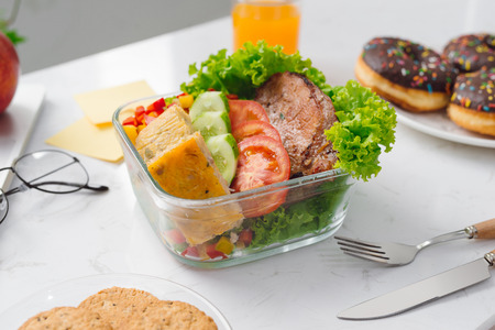 Food in the office. Healthy Vegetable Lunch Box On Working Desk Banco de Imagens