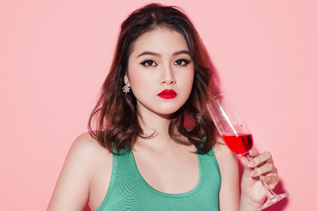 Happy fashion asian woman drinking champagne over pink background. Stock Photo