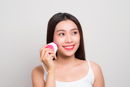 Skin Care. Side portrait of the charming healthy fresh woman with natural make-up using the electric facial massager at isolated white background. Stock fotó