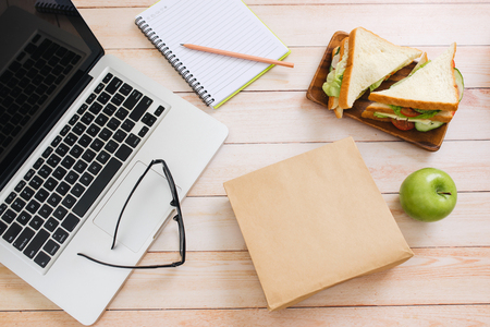 Lunch bag with sandwich and fruits in office table
