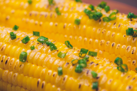 Barbecued corn cobs with herbs on a wooden table Standard-Bild - 101863247