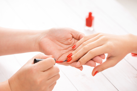 Woman getting nail manicure. Manicurist applying red nail polish to customer.