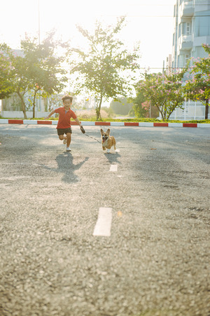Kid boy runs on street with his pet dog