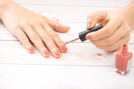 Female hands with red manicure and an open bottle of varnish on the table