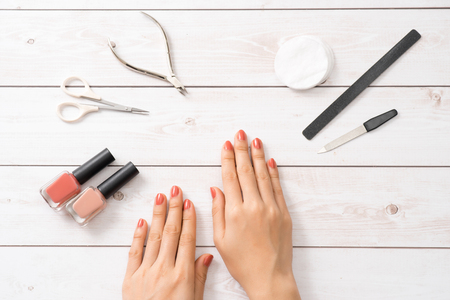 Female hands applying purple nail polish on wooden table with towel and nail set 스톡 콘텐츠 - 102053275