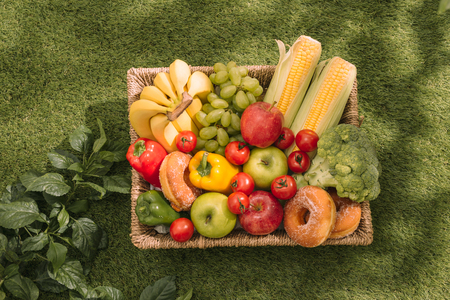 Picnic on the grass. Red checked tablecloth, basket, healthy food sandwich and fruit, orange juice. Top view. Summer Time Rest. Flat lay. Stock Photo