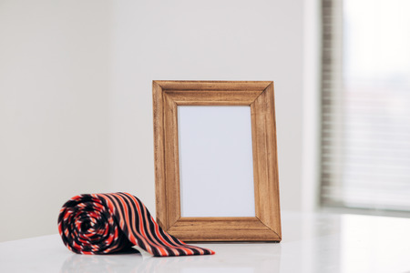 Fathers day composition. Blank frame and tie with space for text on wooden table top Stock Photo