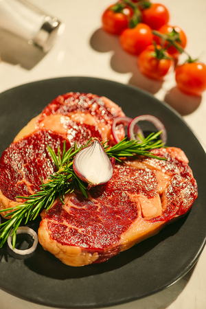 Raw fresh beef on white stone background, top view