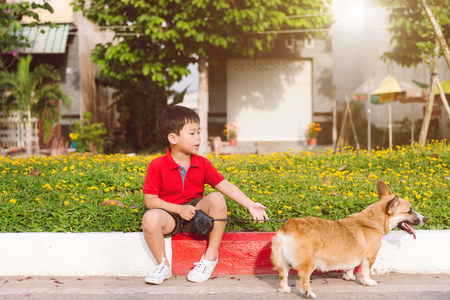Child lovingly embraces his pet dog, a pembroke corgi
