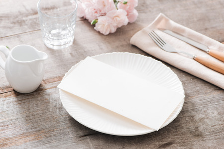 Spring table decoration with flowers. White plates, fork, knife on wooden plate