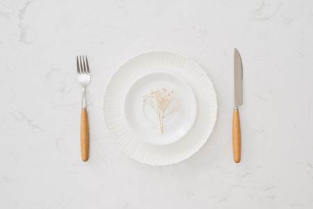 Eating concept. Spoon, fork and white dish on white stone background.