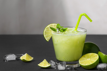 Cocktail juice with lime, mint and ice. Bar drink accessories on black table background. Stock Photo