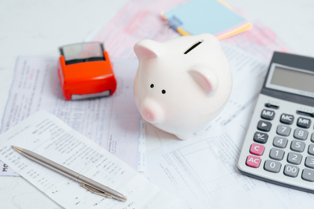 Pen on pile of paper chart and graph with calculator and pink piggy bank on table as finance, money budget, saving or investment planning concept.