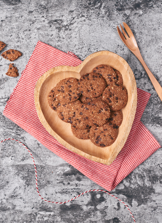 Cookies on wooden heart-shaped plate. Gift for Valentines Day. Stock Photo