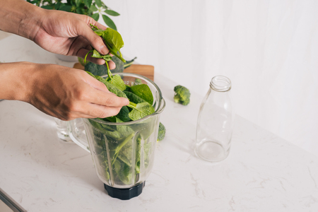 Making green smoothie. Natural, organic healthy juice in bottle for weight loss diet Stock Photo - 102764635