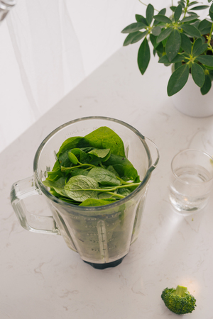 Making green smoothie. Natural, organic healthy juice in bottle for weight loss diet