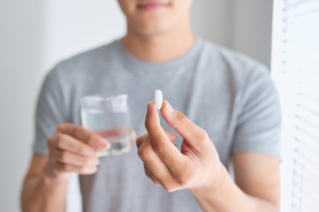 Happy asian man holding a pill and a glass of water looking at camera Stockfoto