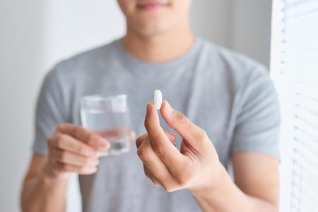 Glücklicher asiatischer Mann, der eine Pille und ein Glas Wasser hält Kamera betrachtet