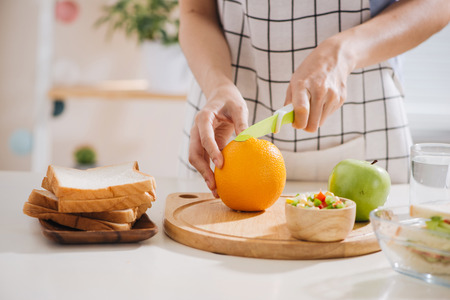 Hands of a woman is making school lunch box. It is more interesting for children. Stock Photo