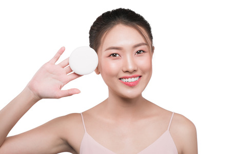Cute girl with black hair holding powder puff. Skin care concept