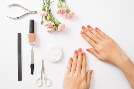 Female hands applying purple nail polish on wooden table with towel and nail set 写真素材