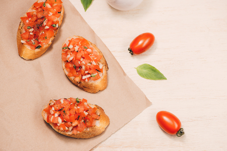 Simple italian appetizing bruschetta with tomato, on wooden table