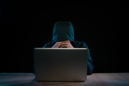 Hacker in a dark hoody sitting in front of a notebook. Computer privacy attack