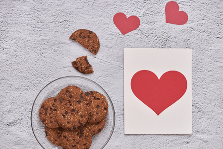 Homemade chocolate cookies on glass plate and heart shape paper card. Valentines day concept. Stock Photo