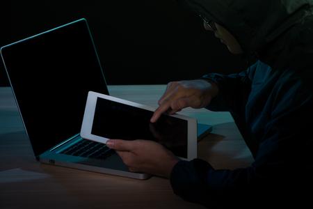 Hooded cyber crime hacker using digital tablet internet hacking in to cyberspace