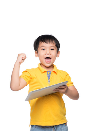 Portrait of cheerful boy with backpack holding digital tablet with hand raised Stock Photo