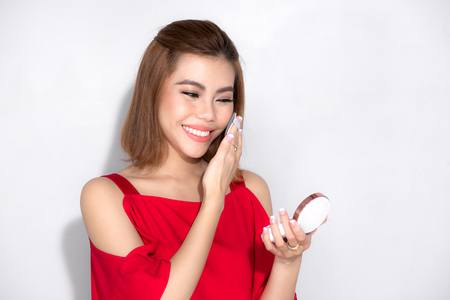 Beautiful asian woman standing red dress and holding cosmetic product. Zdjęcie Seryjne