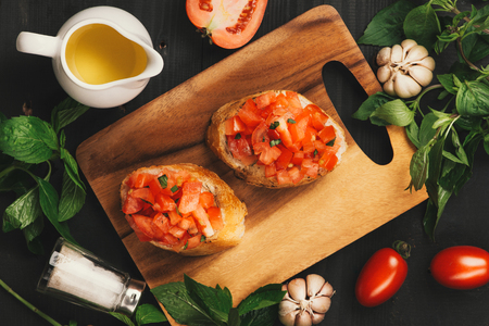 Tasty Italian bruschetta with  bread topped with tomato and herbs on wooden board
